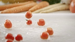 Cherry tomatoes splashing on wet surface in slow motion closeup Stock Footage