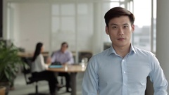 MS Businessman in blue shirt standing in foreground of two colleagues and Stock Footage