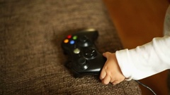 Cute, baby boy playing a computer game pad  Stock Footage