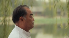 MS Head shot of mature man smiling and laughing outdoors / China Stock Footage