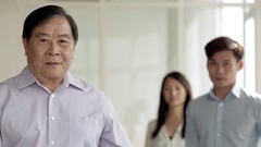 MS Senior business man folding arms with young colleagues behind him / Singapore Stock Footage