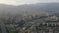 Long shot aerial view of a metropolis day time with mountains in the background Stock Footage