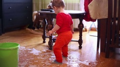 Sweet toddler baby playing with spilled water on the floor at home   Stock Footage