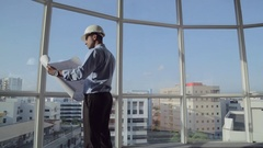 MS SELECTIVE FOCUS Architect with safety helmet stands in office with building Stock Footage