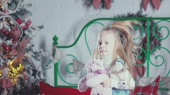 Girl jumping on the bed with a toy in her hands. Christmas gift Stock Footage