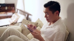 MS Mid-adult man using tablet pc on sofa / Singapore Stock Footage