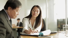 MS Businesswoman writes on note pad and speaks to senior businessman / Singapore Stock Footage