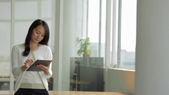 MS SELECTIVE FOCUS Businesswoman leans on desk using a digital tablet / Stock Footage