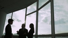 MS Three colleagues stand at window at dusk / Singapore Stock Footage