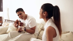 MS SELECTIVE FOCUS Mid-adult man playing guitar on sofa / Singapore Stock Footage