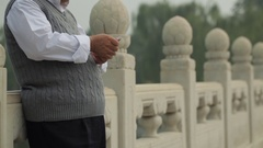 TU MS Mature man talking on mobile phone leaning on stone balustrade / China Stock Footage