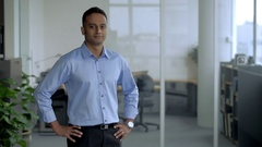 MS SELECTIVE FOCUS Business man stands in front of his office with hands on hips Stock Footage