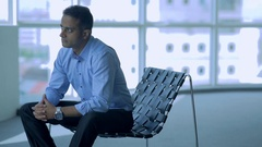 MS SELECTIVE FOCUS Businessman sits with hands clasped in empty office / Stock Footage