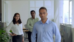 MS R/F Businessman in blue shirt stands in front of his colleagues / Singapore Stock Footage