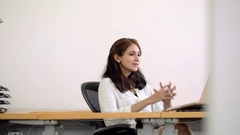 MS SELECTIVE FOCUS PAN Businesswoman folds her hands under her chin at office Stock Footage