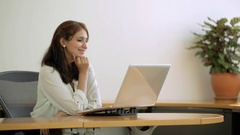 MS SELECTIVE FOCUS PAN Businesswoman sits at desk with hand on her chin, Stock Footage