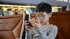 Boy play games on smart phone Stock Footage
