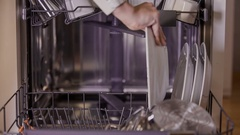 Putting plates and a tray into a dishwasher Stock Footage