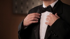 CU TU Portrait of young man fixing his tuxedo and smiling / China Stock Footage