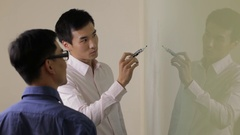 MS Young business man writing on white board, talking to colleague in office / Stock Footage