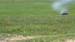 Toy car travels fast on a green grass pasture with white smoke leaving Stock Footage