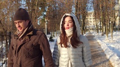 Thoughtful man and woman walking in winter park holding hands Stock Footage