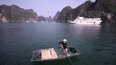 WS Fisherwoman in Ha Long Bay with passenger ship in background / Vietnam Stock Footage