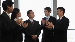 MS Group of business people clapping, standing around senior business man in Arkistovideo