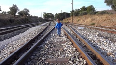 Smiling boy walks along railway track Stock Footage