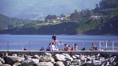 Local youth relaxing on a pier in the harbour. Stock Footage