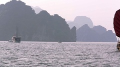 WS PAN Junk boat with red sails and passenger ship in bay / Ha Long Bay, Vietnam Stock Footage