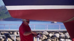 Man painting the bottom of a boat for maintenance Stock Footage