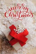 Gift box of kraft paper with Red Ribbon and Merry Christmas text. Calligraphy Stock Photos
