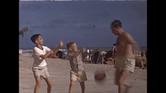 Vintage 16mm film, 1946, California, boys playing ball at beach, nice background Stock Footage