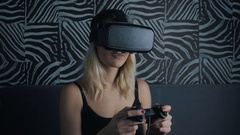 Virtual reality game. Girl with pleasure uses head-mounted display at home Stock Footage