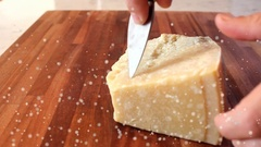 Cutting pieces of parmesan cheese with a knife on a wooden chopping board Stock Footage