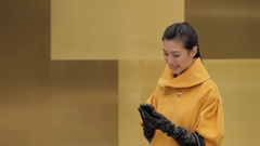 MS Young woman in yellow coat using mobile phone and smiling / China Stock Footage