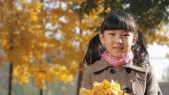 CU Portrait of girl holding dry leaves and smiling at camera in park / China Stock Footage