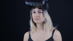 Close-up shot of woman getting experience in using VR-headset in dark room Stock Footage