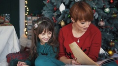 Mother with Daughter near Christmas Tree Stock Footage
