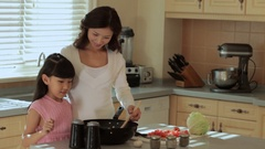 MS Mother and daughter cooking in kitchen / China Stock Footage