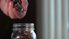 Male hand on an angle drops coins into jar. Stock Footage
