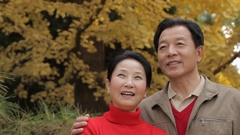 CU Elderly couple smiling and looking at each other, standing in park / China Stock Footage
