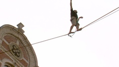 Tightrope Walker Balancing On A Rope between buildings Stock Footage