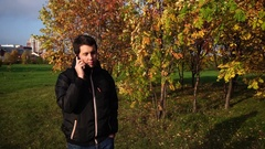 Young man in black jacket walking in the autumn park talking on the phone Stock Footage