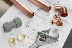 Various Plumbers Tools and Plumbing Materials on Architectural House Plans Stock Photos