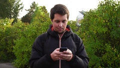 Young man in black jacket surf the internet using his smartphone outdoor Stock Footage