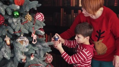 Boy Making Artificial Snow on Christmas Tree Stock Footage