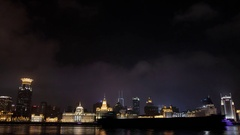 T/L WS Huangpu River with ships passing by and city lights going off on The Bund Stock Footage