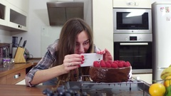 Beautiful brunette girl making pictures of her freshly cooked cake Stock Footage